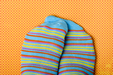 closeup of someone rubbing his or her feet wearing colorful striped-patterned socks, on an orange and yellow patterned background