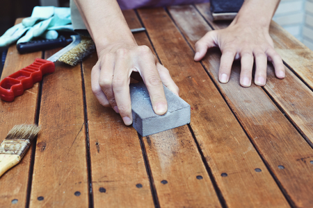sanding block: closeup of a young caucasian man sanding an old wooden table with a sanding block