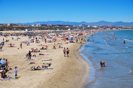 valencian: Valencia, Spain - June 22, 2016: Sunbathers at El Cabanyal and La Malvarrosa beaches in Valencia, Spain. These are the main beaches in the capital of the Valencian Community