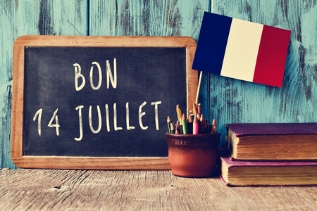 a sign: a wooden-framed chalkboard with the text bon 14 juillet, happy 14th of July, the National Day of France, written in French and a flag of France, against a rustic blue wooden background