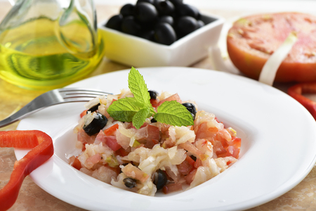 food dish: closeup of a dish of esqueixada de bacalla, a cold dish made with codfish, red pepper, tomato, onion and black olives, and dressed with olive oil, typical of Catalonia, Spain, on a table Stock Photo