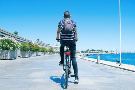 a young caucasian man, seen from behind, cycling by the port of Valencia, Spain