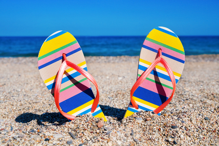 vacationers: closeup of a pair of colorful striped flip-flops with pink straps stuck on the sand of a beach