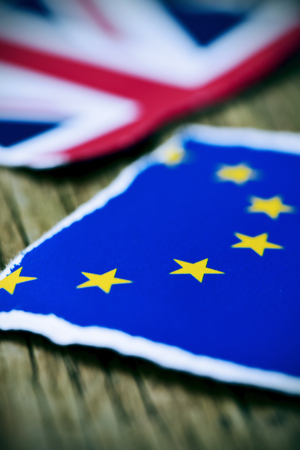EU: the flag of the European Community and the flag of the United Kingdom put together on a rustic wooden surface