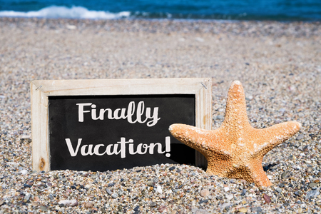 finally: closeup of a starfish and a wooden-framed chalkboard with the text finally vacation written in it, placed on the sand of a beach Stock Photo