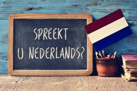 Tablica z pytaniem Spreekt kształcie U Nederlands ?, mówisz po holendersku? napisane w języku polskim, do garnka z kredkami, kilka książek i flagą Holandii na drewniane biurko