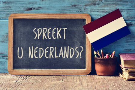 a chalkboard with the question Spreekt u Nederlands?, do you speak Dutch? written in Dutch, a pot with pencils, some books and the flag of the Netherlands on a wooden desk Foto de archivo