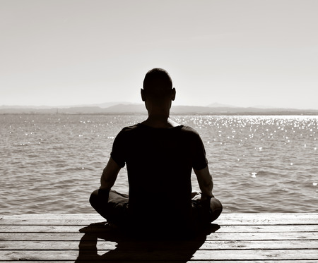yogi aura: young man seen from behind meditating in the lotus position in an old wooden pier over the sea or over a lake, in black and white Stock Photo