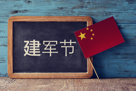 a chalkboard with the text Army Day written in Chinese and the flag of China, on a rustic wooden surface, against a blue wooden background Stock Photo