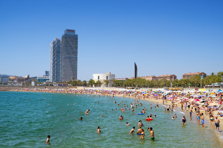frequented: Barcelona, Spain - July 10, 2016: People at Nova Icaria Beach in Barcelona, Spain, and Hotel Arts and Mapfre Tower in the background. This busy beach is mainly frequented by the locals