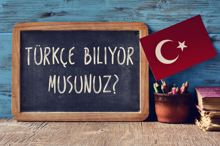 a chalkboard with the question turkce biliyor musunuz?, do you speak Turkish? written in Turkish, a pot with pencils, some books and the flag of Turkey, on a wooden desk