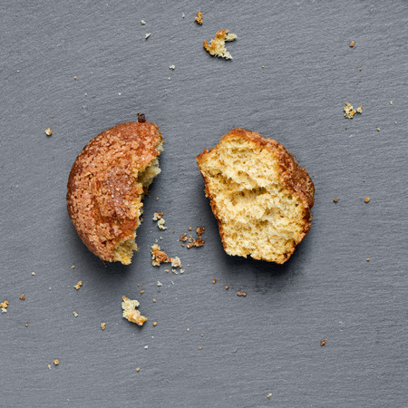 madeleine: high-angle shot of a plain muffin broken in two pieces on a slate background