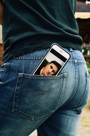 derision: a smartphone with a picture of a young man sticking his tongue out in its screen, taken by myself, placed on the back pocket of the jeans of a young man