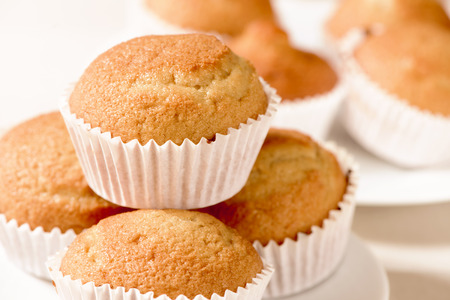muffin: closeup of some appetizing plain muffins in a white ceramic plate on a set table