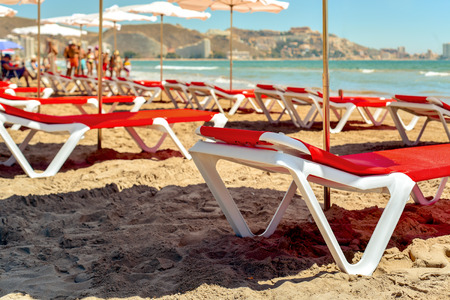 vacationers: closeup of some sunloungers and umbrellas in San Antonio Beach in Cullera, Spain, with the Mediterranean sea and some unrecognizable sunbathers and walkers in the background