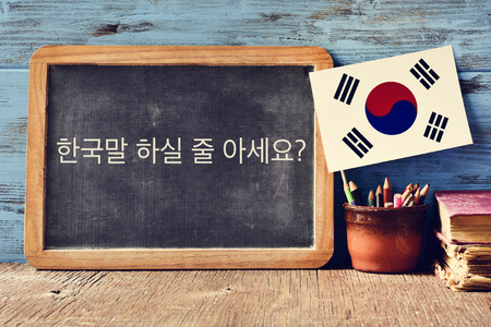 a chalkboard with the question do you speak Korean? written in Korean, a pot with pencils, some books and the flag of South Korea, on a wooden desk 스톡 콘텐츠