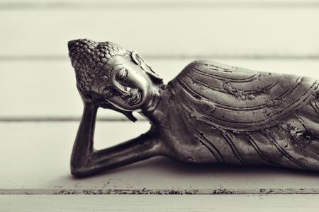 gautama buddha: closeup of a representation of the buddha laying down, on a pale green rustic background
