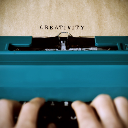 essayist: closeup of the hands of a young man typewriting the word creativity in a yellowish foil with an old blue typewriter