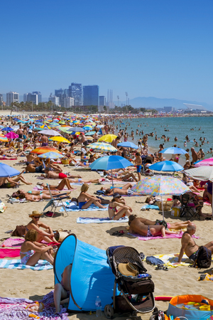 frequented: Barcelona, Spain - July 10, 2016: Sunbathers at Platja del Bogatell beach in Barcelona, Spain, with the Parc del Forum in the background. This busy beach is mainly frequented by the locals