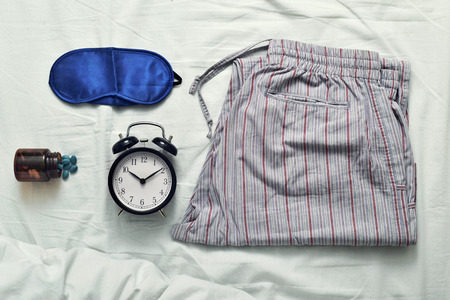 sleeping pills: high-angle shot of a sleep mask, a bottle of sleeping pills, an alarm clock and a pajamas on a bed covered with a white bedsheet Stock Photo
