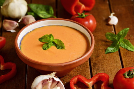 andalusian cuisine: an earthenware bowl with spanish gazpacho and some vegetables to prepare it such as tomato, red pepper or garlics on a rustic wooden table
