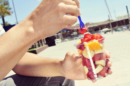 comiendo frutas: Primer plano de un hombre caucásico joven comer una ensalada de frutas en un vaso de plástico transparente al aire libre