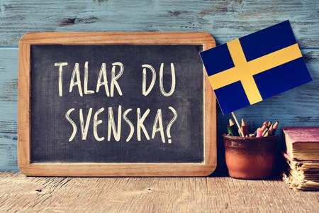 a chalkboard with the question talar du svenska?, do you speak Swedish? written in Swedish, a pot with pencils, some books and the flag of Sweden, on a wooden desk Reklamní fotografie