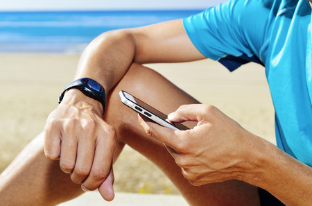 syncing: closeup of a young man wearing sport clothes syncing his smartphone and his smartwatch