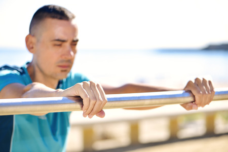 to incline: closeup of a young caucasian sportsman wearing sport clothes doing incline push-ups outdoors next to the sea