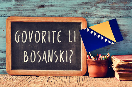 bosna and herzegovina: a chalkboard with the question govorite li bosanski?, do you speak Bosnian? written in Bosnian, a pot with pencils, some books and the flag of Bosnia and Herzegovina, on a wooden desk Stock Photo