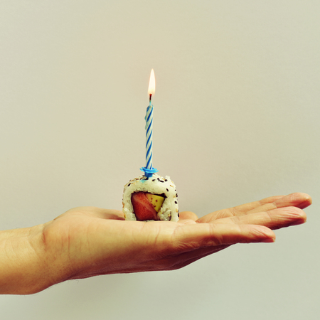 california roll: closeup of the hand of a young man holding a California roll topped with a lit cake candle, against an off-white background
