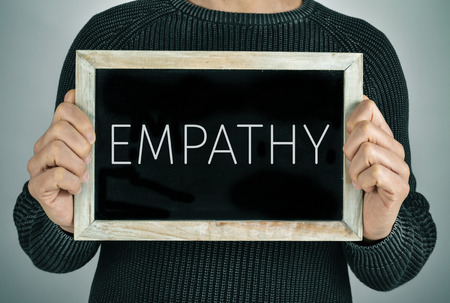 adequacy: closeup of a young caucasian man showing a chalkboard with the text empathy written in it Stock Photo