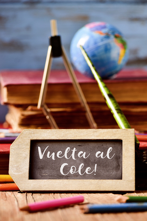 cole: label-shaped chalkboard with the text vuelta al cole, back to school in spanish, some old books and old stationery such as a pen nib or pencils crayons of different colors, on a rustic wooden surface