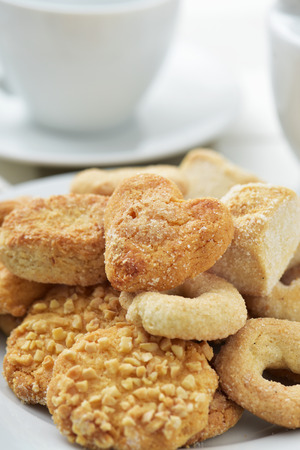coffeetime: closeup of an assortment of different shortbread biscuits in a white plate, on a set table with some cups of tea or coffee