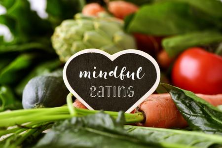 close-up van een hart-vormige bord met de tekst bewust eten geplaatst op een stapel van een aantal verschillende rauwe groenten, zoals komkommers, tomaten, wortelen, artisjokken, groene paprika's en courgettes