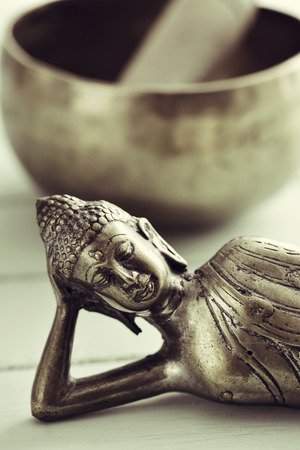 rin gong: closeup of a representation of the buddha laying down, on a pale green rustic background, and a singing bowl with its mallet in the background Stock Photo