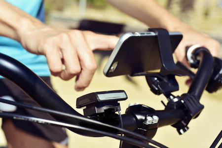 closeup of a young man using a smartphone mounted in the handlebar of a bicycle