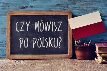 schoolroom: a chalkboard with the question czy mowisz po polsku?, do you speak Polish? written in Polish, a pot with pencils, some books and the flag of Poland