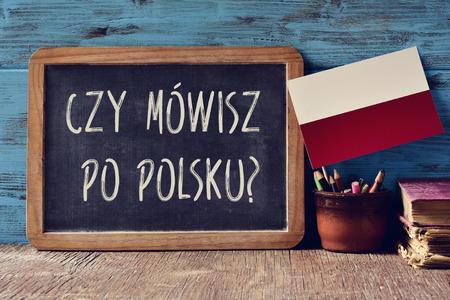 una lavagna con la domanda czy mowisz po polsku ?, parli polacco? scritto in polacco, una pentola con matite, alcuni libri e bandiera della Polonia