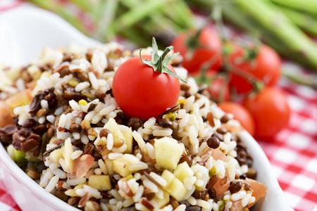 close-up van een kom met verfrissende linzen en rijst salade in een tafel met een geruit tafelkleed