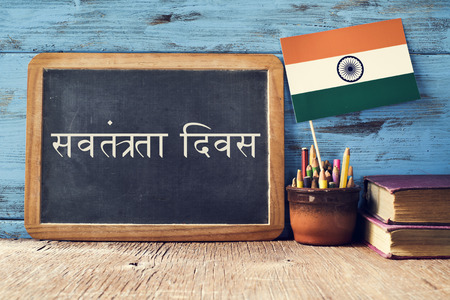 devanagari: a chalkboard with the text Independence Day written in Hindi and a flag of India, on a rustic wooden surface, against a blue wooden background