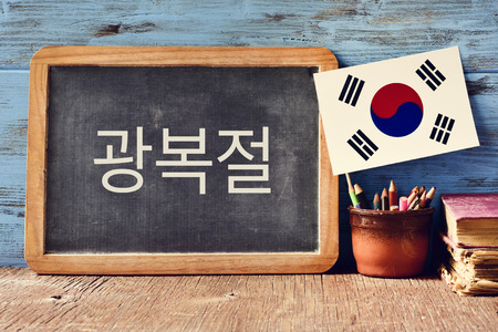 a chalkboard with the text National Liberation Day of Korea written in Korean and a flag of South Korea, on a rustic wooden surface, against a blue wooden background