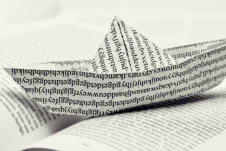 nonsense: closeup of a paper boat, made with a printed paper with non-sense words, on an open book