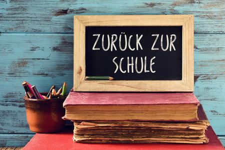 portarretrato de una pizarra con el texto zur Schule Zuruck, de vuelta a la escuela, escrito en alemán, en una pila de libros antiguos y una olla con unos lápices, contra un fondo azul de madera rústica
