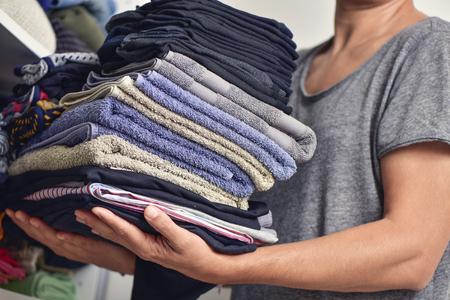 soltería: Primer plano de un hombre joven que lleva una pila de ropa doblada diferentes