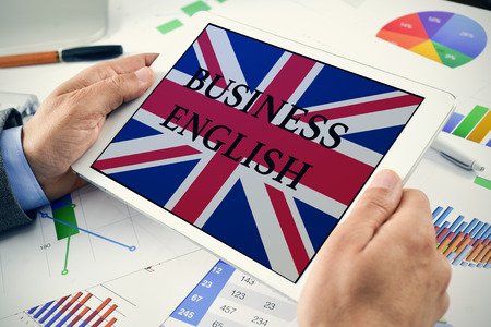 closeup of a young caucasian businessman at his office desk full of charts showing a tablet computer with the text business English and the flag of United Kingdom in its screen Stock Photo