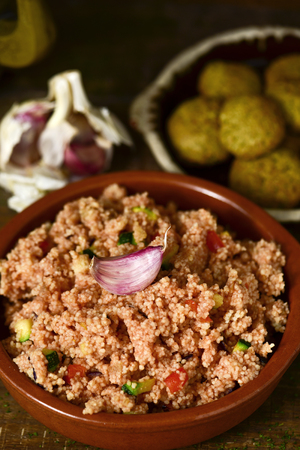 grits: closeup of an earthenware casserole whit couscous with vegetables and some falafel in a plate in the background, on a wooden table Stock Photo
