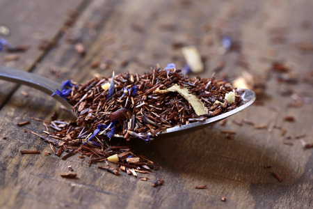 rooibos: closeup of a spoon with rooibos tea mixed with flowers, dry fruits and herbs, on a rustic wooden table Stock Photo
