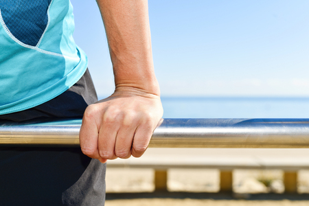strong chin: closeup of a young caucasian sportsman wearing sport clothes doing exercises in a metal bar outdoors Stock Photo