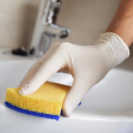soltería: Primer plano de un hombre joven que limpia el fregadero del cuarto de baño con una esponja de fibra y desinfectante